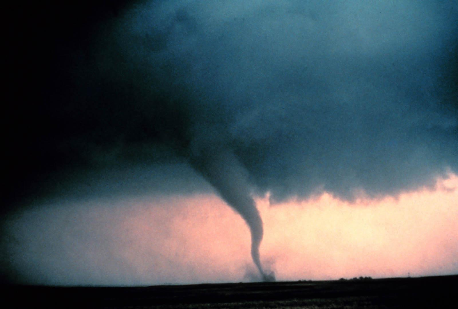 Tornado with dust and debris cloud forming at the surface