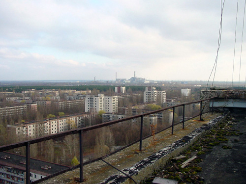 The abandoned city of Pripyat with the Chernobyl plant in the distance
